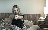 Anxious woman sitting in her bed pointing a pistol at viewer - FC000714