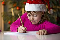 Little girl with Christmas cap writing a Christmas list - ROMF000121