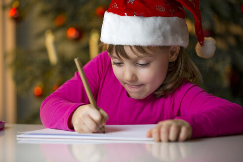 Little girl with Christmas cap writing a Christmas list - ROMF000121