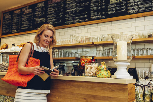 Smiling blond woman standing at counter in a coffee shop looking at a booklet - CHAF001012