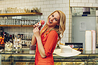 Portrait of laughing blond woman standing at counter in a ice cream parlour with ice cream cone - CHAF001015