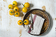 Yellow tomatoes with a knife on a wooden board - ODF001153