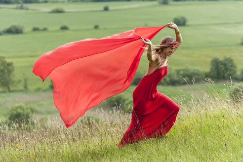 Woman in red dress running on a meadow with red cloth - TCF004766