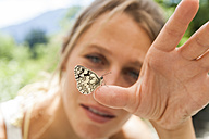 Butterfly on woman's hand - TCF004772