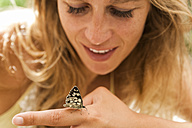 Butterfly on woman's hand - TCF004775