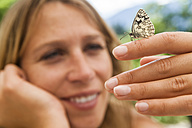 Butterfly on woman's hand - TCF004777