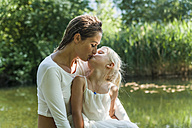 Mother and daughter kissing at a lake - TCF004787