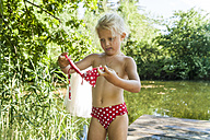 Girl putting on bikini standing on jetty at a lake - TCF004789