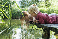 Mother and daughter lying on jetty at a lake looking at water - TCF004799