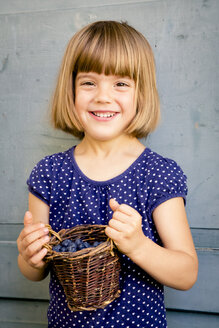 Portrait of little girl with wickerbasket of blueberries - LVF003737
