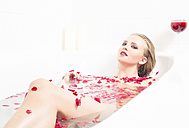 Young woman relaxing in rose petal bath - FC000718