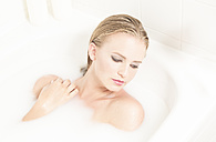 Young woman relaxing in milk bath - FC000719