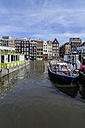 Netherlands, Amsterdam, Houses at town canal, tour boats in foreground - THA001421