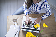 Young woman using laptop, working from home - RIBF000177