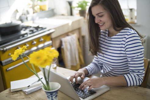 Young woman using laptop, working from home - RIBF000180