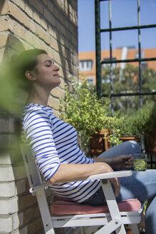 Young woman sitting on balcony, drinking tea, eyes closed - RIBF000186
