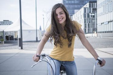 Germany, Cologne, portrait of smiling young woman with blowing hair on her bicycle - RIBF000213