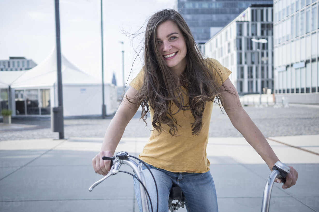Germany, Cologne, portrait of smiling young woman with blowing hair on her bicycle - RIBF000213 - Richárd Bellevue/Westend61