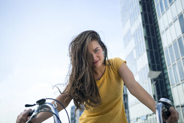 Germany, Cologne, portrait of smiling young woman on her bicycle - RIBF000216