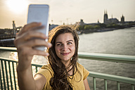 Germany, Cologne, young woman standing on Rhine bridge taking a selfie with her smartphone - RIBF000231