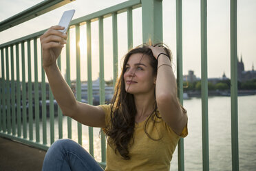Germany, Cologne, young woman sitting on Rhine bridge taking a selfie with her smartphone - RIBF000234