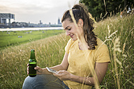 Germany, Cologne, woman with beer bottle and smartphone relaxing on a meadow near Rhine River - RIBF000224