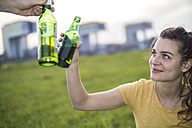 Germany, Cologne, woman toasting with beer bottle on a meadow at evening twilight - RIBF000246