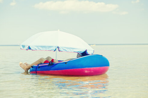 Germany, Niendorf, young boy relaxing in an inflatable boat - MEMF000903