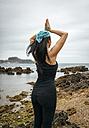 Spain, Asturias, Gijon, woman doing yoga on a rocky beach - MGOF000390