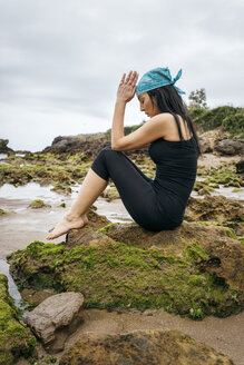 Spain, Asturias, Gijon, woman doing yoga on a rocky beach - MGOF000375