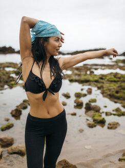 Spain, Asturias, Gijon, woman doing yoga on a rocky beach - MGOF000377