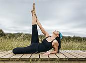 Spain, Asturias, Gijon, woman doing yoga outdoors - MGOF000387