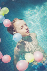 Boy in swimming pool surrounded by balloons floating in water - SARF002068