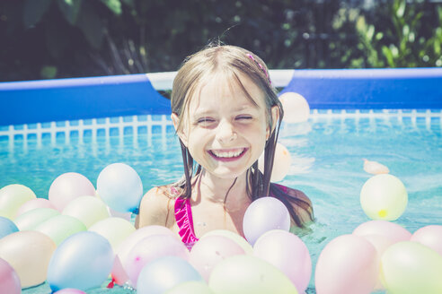 Happy girl in swimming pool surrounded by balloons - SARF002069