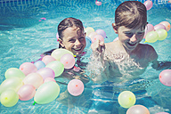 Happy boy and girl in swimming pool surrounded by balloons - SARF002072