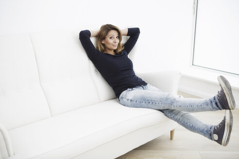 Woman sitting on white couch with legs in the air - GDF000833