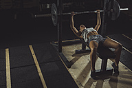 Female athlete doing bench presses with barbell - MADF000473