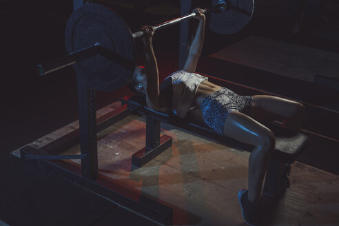Female athlete doing bench presses with barbell - MADF000474