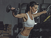 Portrait of a female athlete training with dumbbells in gym - MADF000483
