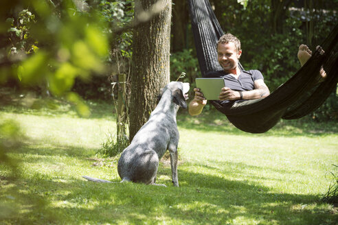 Relaxed man lying in hammock with digital tablet and dog beside him - ONF000831