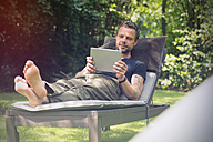 Relaxed man lying in sun lounger in garden using digital tablet - ONF000834