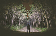 Back view of a man standing on forest track at night illuminating the woods with a flashlight - RAEF000236