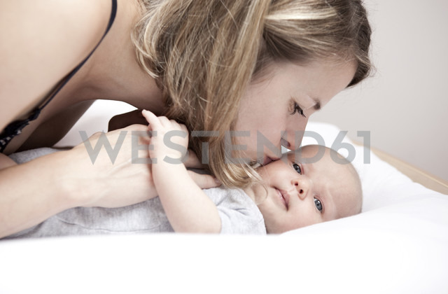 Young woman kissing baby lying on changing table - MFRF000294 - Michelle Fraikin/Westend61