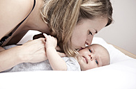 Young woman kissing baby lying on changing table - MFRF000294
