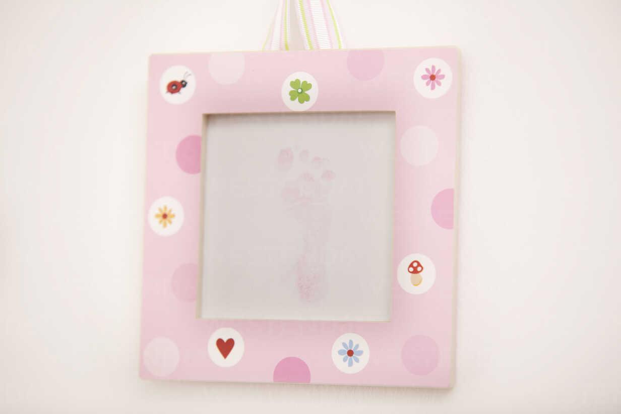 Pink picture frame with footprint of a newborn girl - MFRF000300 - Michelle Fraikin/Westend61