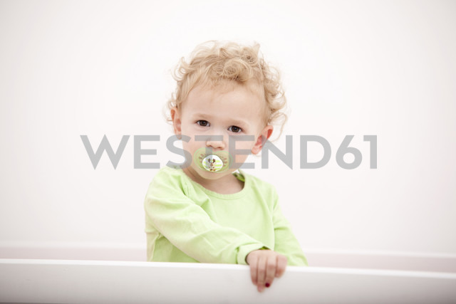 Portrait of little blond girl with pacifier standing in cot - MFRF000301 - Michelle Fraikin/Westend61