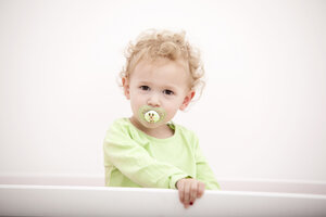 Portrait of little blond girl with pacifier standing in cot - MFRF000301