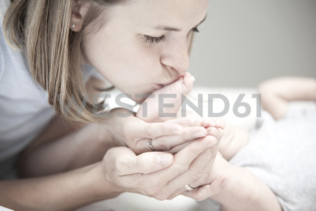 Young mother kissing foot of baby girl - MFRF000307