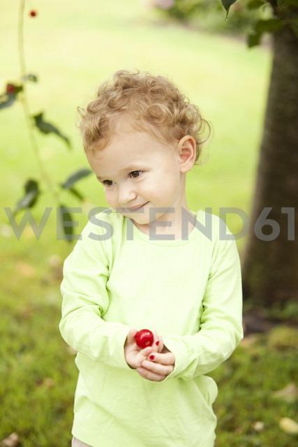 Portrait of little girl holding cherry in her hand - MFRF000310