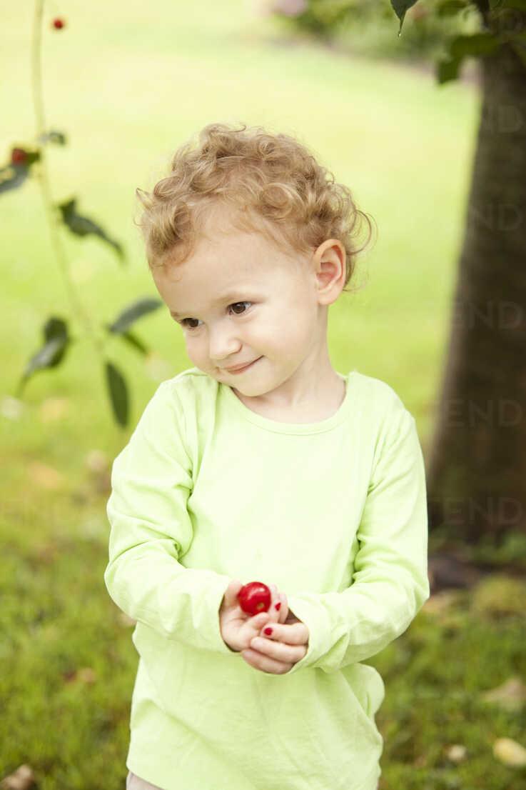 Portrait of little girl holding cherry in her hand - MFRF000310 - Michelle Fraikin/Westend61